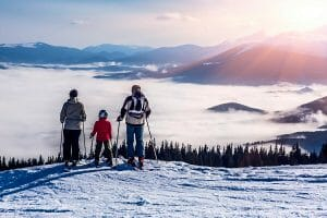 family skiing looking out over mountains