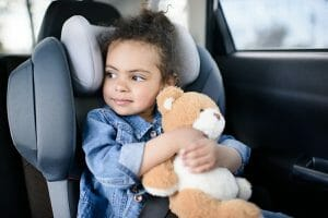 child in car seat holding teddy bear