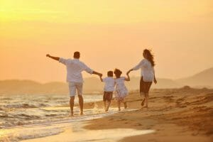 family on a beach at sunset