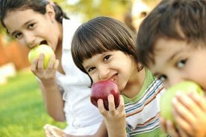 Kids sitting in a row eating apples