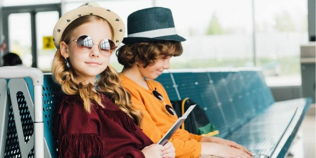 Two girls in hats sitting in airplane terminal.
