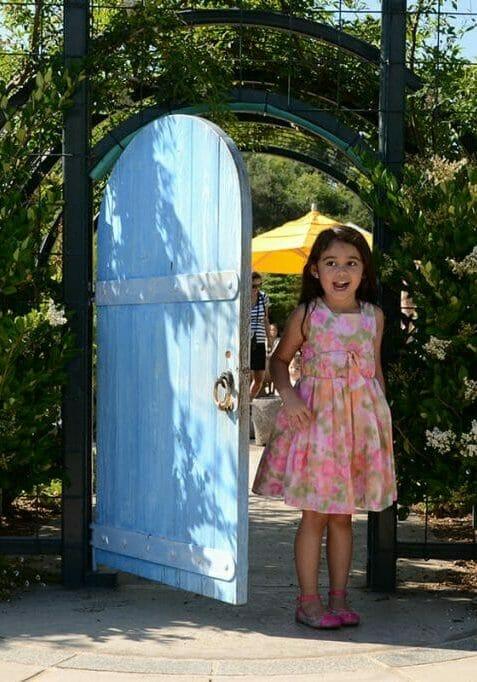 A kid-sized blue door leads to the children's garden.