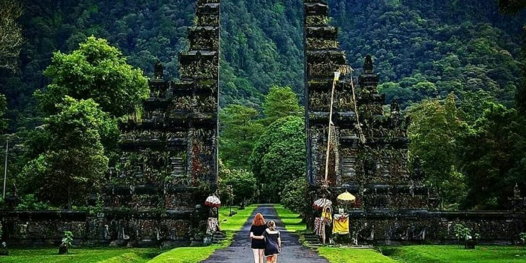 Two girls walking to temple gate in Southeast Asia