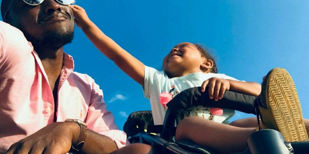 Dad kneeling next to kid in stroller