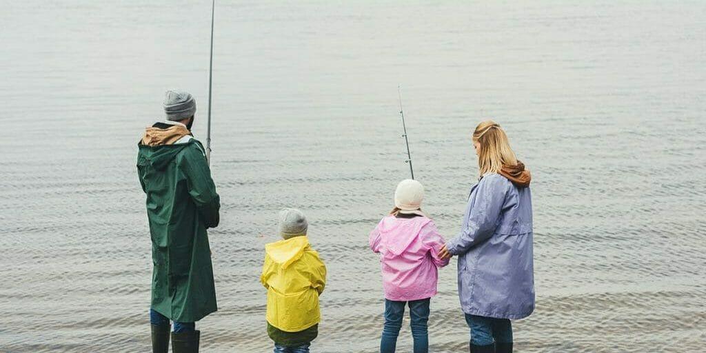 Family of four fishing on coast