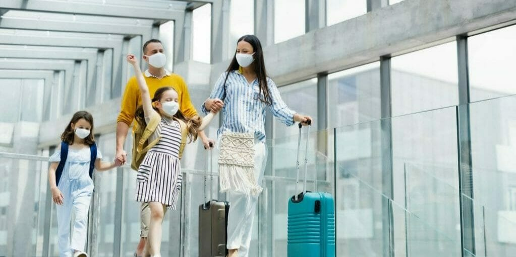 Family with two kids in airport wearing masks