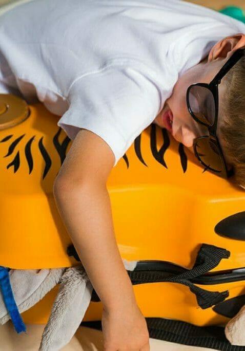 Tired kid asleep on suitcase