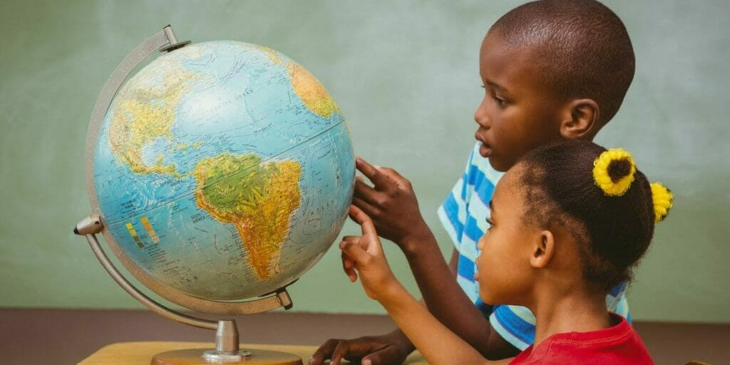 Two children pointing at globe in classroom